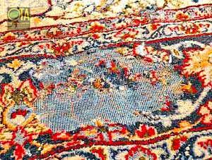 Ausgefressene Stellen in Teppichflor von den Motten in einem antiken Teppich