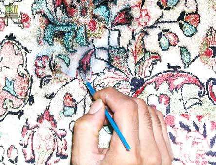 Flecken im Seidenteppich werden mit Pinsel schonend entfernt