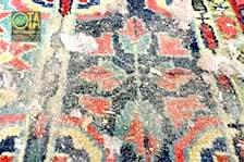 Klopfen eines Wollteppichs vor der Teppichreinigung